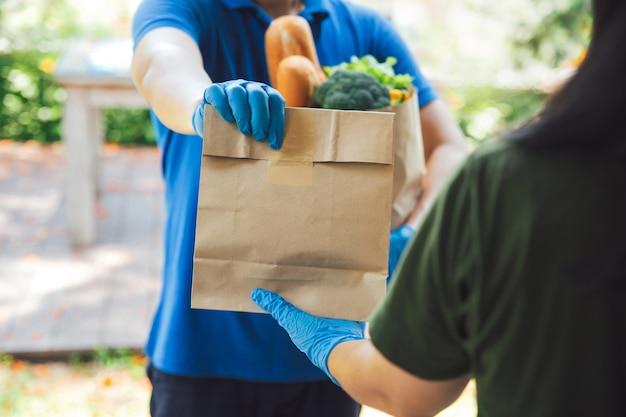 Człowiek dostawy w rękawiczkach higienicznych w niebieskim mundurze przekazanie torby żywności, owoców, warzyw do odbiorcy