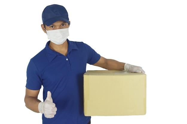 Człowiek dostawy w rękawiczkach z maską medyczną i trzymający pudełko w ręku na białym