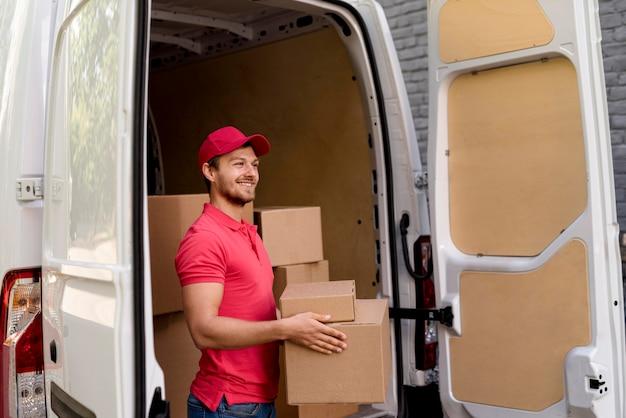 Człowiek dostawy w samochodzie niosącym paczki