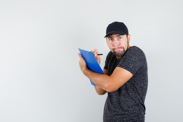 Człowiek dostawy w t-shirt i czapkę, robienie notatek w schowku i zabawny wygląd