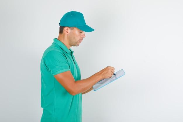 Człowiek dostawy w zielonej koszulce i czapce, robiąc notatki na pokładzie i patrząc zajęty