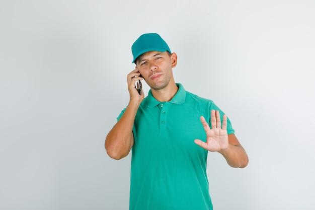 Człowiek dostawy w zielonej koszulce z czapką rozmawia przez telefon ze znakiem stop