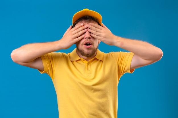 Człowiek dostawy w żółtej koszulce polo i czapce stożkowe oczy z rękami dla niespodzianki stojącej na odosobnionym niebieskim