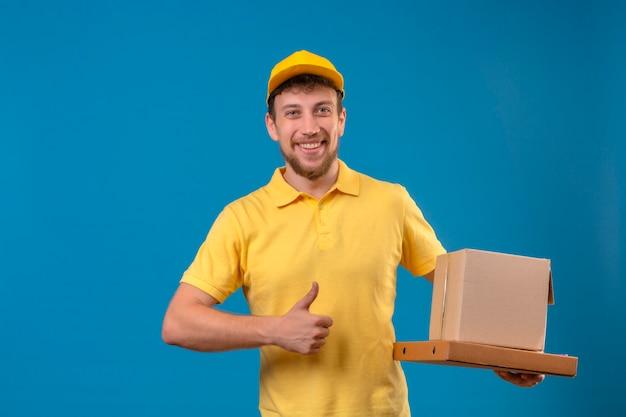 Człowiek dostawy w żółtej koszulce polo i czapce, trzymając pudełka po pizzy i opakowanie pudełko z siebie zadowolony i szczęśliwy pokazując kciuki do góry stojąc na niebiesko