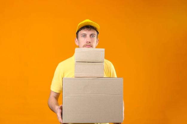 Człowiek dostawy w żółtej koszulce polo i czapce trzymającej duże ciężkie pudła wyglądające na zmęczonego i znudzonego stojącego na odizolowanej pomarańczy