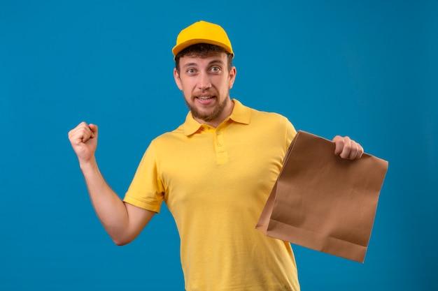 Człowiek dostawy w żółtej koszulce polo i czapce trzymającej papierowy pakiet podnosząc pięść z koncepcją zwycięzcy szczęśliwej twarzy stojącej na niebiesko