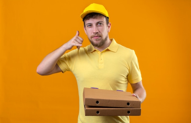 Człowiek dostawy w żółtej koszulce polo i czapce trzymający pudełka po pizzy robiąc zadzwoń do mnie gest wyglądający pewnie uśmiechnięty przyjazny stojący na pomarańczowo