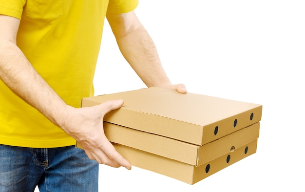 Człowiek dostawy w żółtej koszuli przewożących pudełka pizzy na białym tle. usługa dostawy fast food.