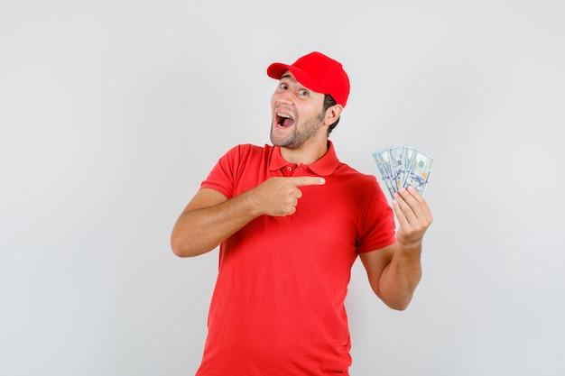 Człowiek dostawy wskazując na banknoty dolara w czerwonej koszulce