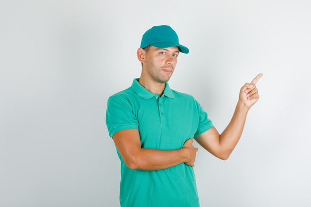 Człowiek dostawy, wskazując na bok w zielonej koszulce z czapką i wyglądający pewnie.