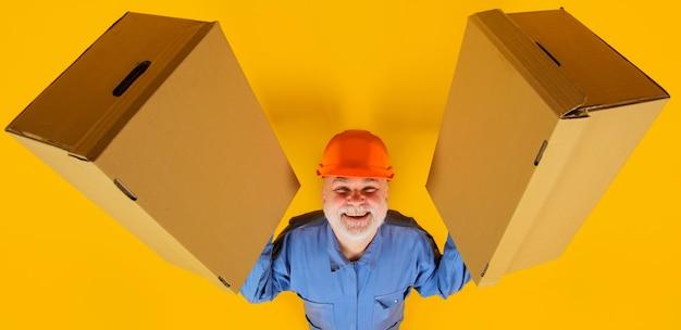 Człowiek dostawy z kartonów. wysyłka. dostawa ze sklepu. uśmiechnięty brodaty mężczyzna z pudełkiem.