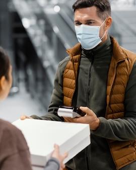 Człowiek dostawy z maską i klientem płacącym
