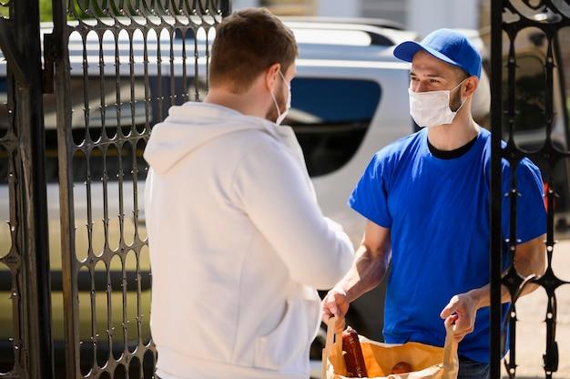 Człowiek dostawy z maską twarz rozdaje artykuły spożywcze