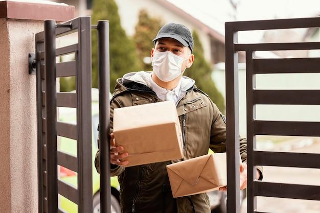 Człowiek dostawy z pakietem na sobie maskę