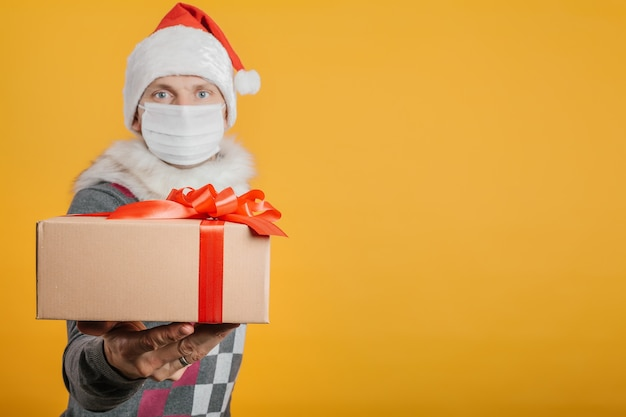 Człowiek dostawy z prezentem w wigilię bożego narodzenia w masce koronawirusa