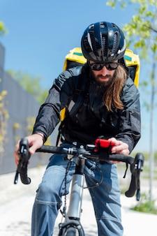 Człowiek dostawy z rowerem działa na smartfonie