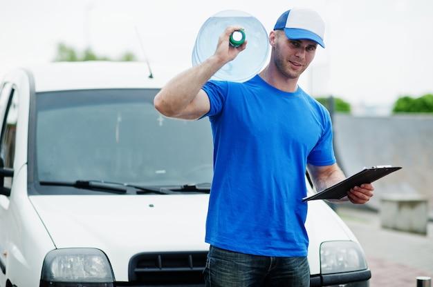 Człowiek dostawy z schowkiem przed furgonetką dostarczającą butelki wody