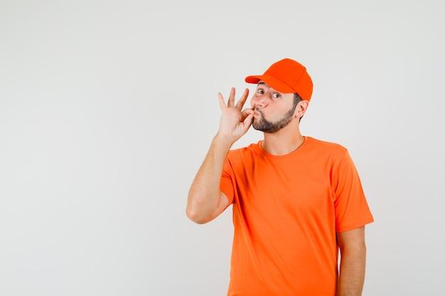 Człowiek dostawy zapinający usta zamknięte w pomarańczowy t-shirt, czapka, widok z przodu.