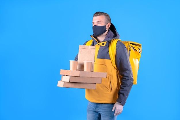 Człowiek dostawy żywności w masce medycznej w żółtej kurtce