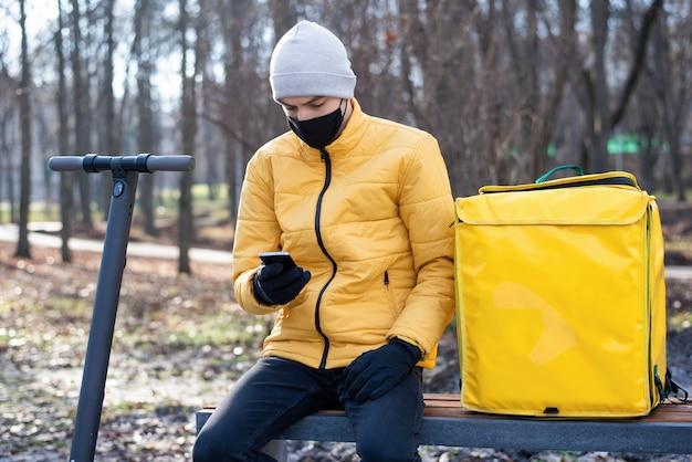 Człowiek dostawy żywności ze skuterem w parku, siedząc na ławce i używając swojego smartfona. czarna maska medyczna, żółty plecak i kurtka. zimowy