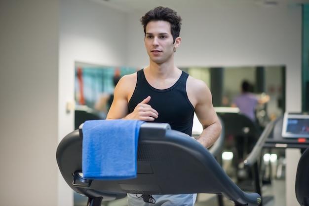 Człowiek działa na bieżni w siłowni, koncepcja treningu cardio