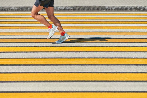 Człowiek działa przejściem dla pieszych, kopia przestrzeń. lekkoatletycznego mężczyzna joggingu w odzieży sportowej na drodze miasta. zdrowy tryb życia, fitness sport hobby