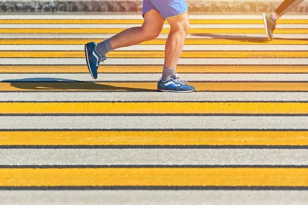 Człowiek działa przejściem dla pieszych, miejsce. lekkoatletycznego mężczyzna joggingu w odzieży sportowej na drodze miasta. zdrowy tryb życia, fitness sport hobby. wykroczenie drogowe. street workout, sprint na świeżym powietrzu