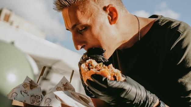 Człowiek enjoing festiwal jedzenia ulicznego na świeżym powietrzu, wydarzenie piwa i burgera. bitwa na burgery