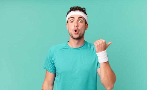 """Człowiek fitness wyglądający na zdziwionego z niedowierzaniem, wskazujący na obiekt z boku i mówiący """"wow, niewiarygodne"""""""
