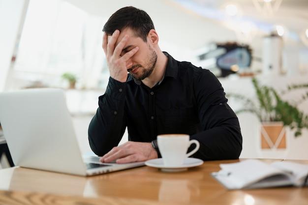 Człowiek freelancer facepalming. praca zdalna z kawiarni. młody biznesmen w czarnej koszuli sprawia, że gest facepalm przed swoim nowoczesnym laptopem. kawiarnia na backgorund.