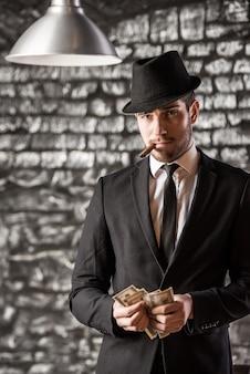Człowiek gangstera pali kubańskie cygaro.