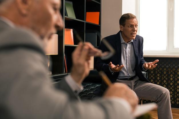 Człowiek gniewny. niezrównoważony zły żonaty mężczyzna gestykuluje siedząc w gabinecie psychoterapeutów i patrząc w dal