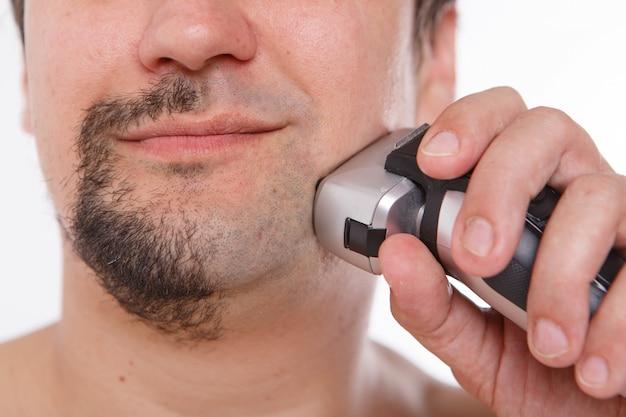 Człowiek goli swój zarost. facet czyści brodę elektryczną maszynką do golenia. poranne zabiegi w łazience.