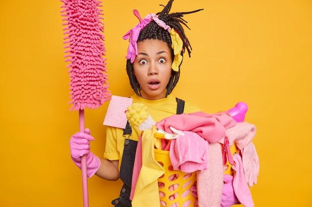 Człowiek gotowy do czyszczenia niesie mop kosz na pranie wygląda z niewiarygodnym wyrazem twarzy ubrany w onalls gumowe rękawiczki odizolowane na żywym żółtym