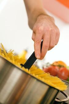 Człowiek gotuje makaron