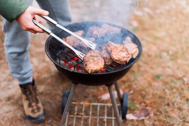 Człowiek gotuje, tylko ręce, grilluje mięso lub stek na danie. pyszne grillowane mięso z grilla. weekend przy grillu. selektywne ustawianie ostrości.