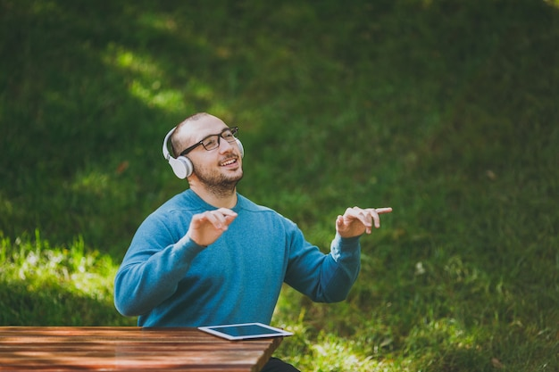 Człowiek gra palcami w powietrzu jak fortepian. student w okularach dorywczo niebieskiej koszuli siedzący przy stole ze słuchawkami, tablet w parku miejskim, słuchanie muzyki, odpoczynek na świeżym powietrzu na łonie natury. koncepcja wypoczynku stylu życia.