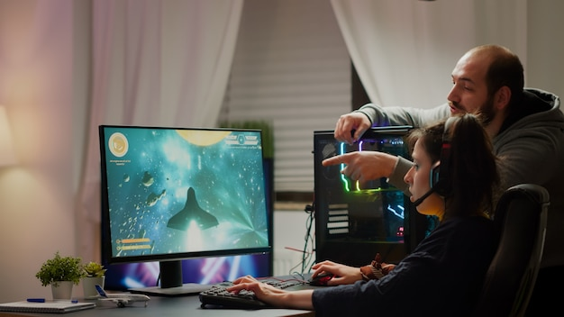 Człowiek-gracz uczący swoją dziewczynę grania w kosmiczną strzelankę na potężnym komputerze osobistym rgb. pro cyber kobieta z zestawem słuchawkowym wykonująca gry wideo przesyłane strumieniowo z domu podczas turnieju online
