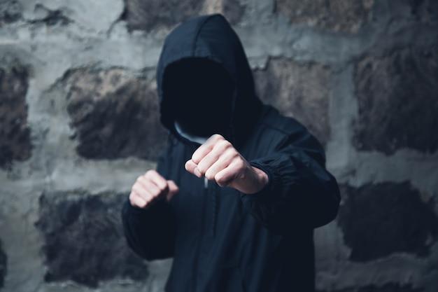 Człowiek haker pięści na czarnej ścianie z cegły