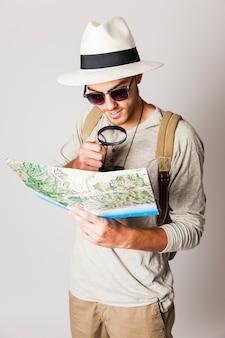 Człowiek hipster przy użyciu lupy do czytania mapy