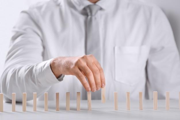 Człowiek i kawałki domina na stole. koncepcja zarządzania