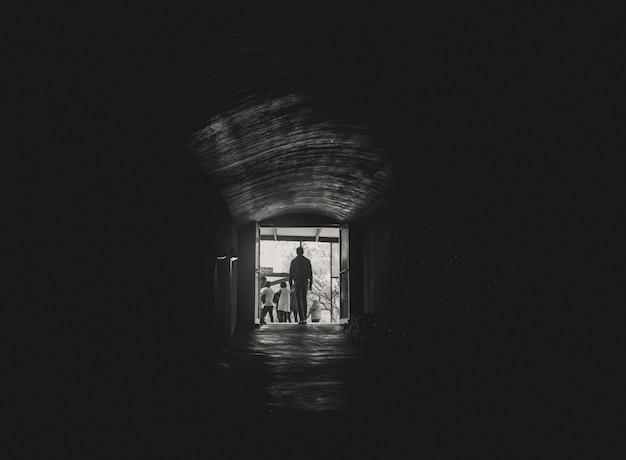 Człowiek idący w kierunku światła na końcu tunelu