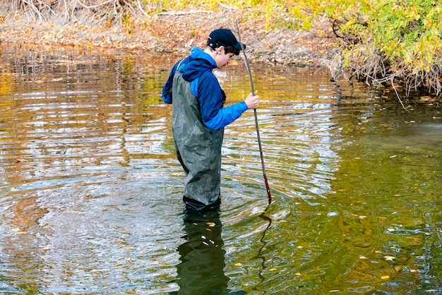 Człowiek idzie bród przez rzekę w mundurze ochronnym