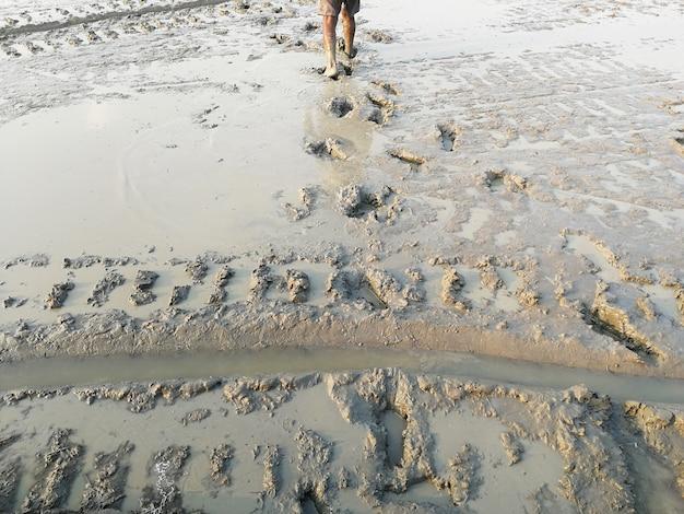 Człowiek idzie i drukuje wiele stóp na brudnej, błotnistej ziemi