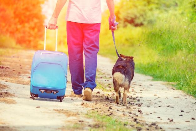 Człowiek idzie z psem na smyczy na polnej drodze latem z powrotem do aparatu. mężczyzna trzymający torbę podróżną
