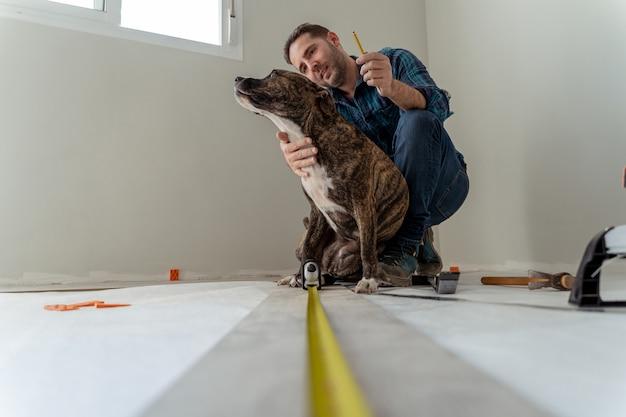 Człowiek instaluje drewnianą podłogę bawiąc się z psem