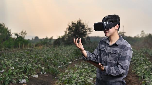 Człowiek inteligentny rolnik stojący w zielonym polu i noszenie technologii okularów rzeczywistości wizualnej.
