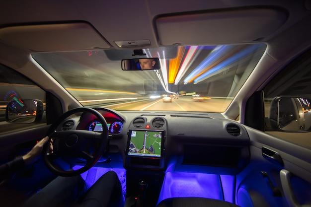 Człowiek jazdy z nawigacją na autostradzie miasta. wieczorna pora nocna
