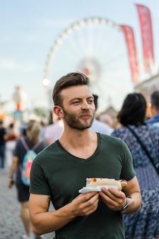 Człowiek jedzenie ulicy żywności. uliczne hotdogi
