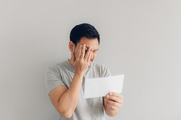 Człowiek jest nienawidzony i smutny z powodu białej wiadomości pocztowej lub rachunku.